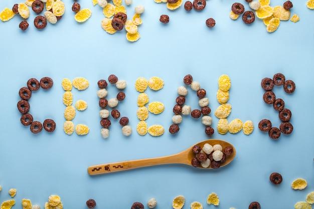 Getreide-konzept. löffel mit glasierten schokoladenbällchen, ringen und cornflakes zum gesunden trockenen frühstück auf einer blauen brandung Premium Fotos