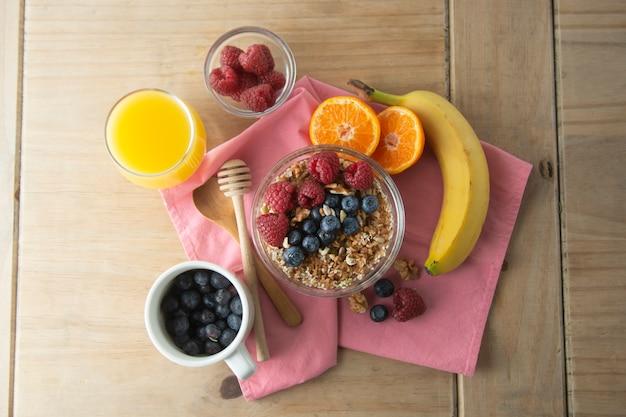 Getreide mit früchten, beeren zum frühstück. gesundes frühstück, hölzerner hintergrund. Premium Fotos