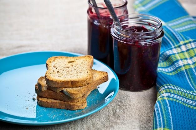 Getreidebrotscheiben auf blauer keramikplatte und selbst gemachter kirsch- und waldbeerenmarmelade Premium Fotos