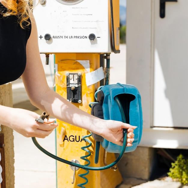Getreidefrau, die luftpumpe an der tankstelle hält Kostenlose Fotos