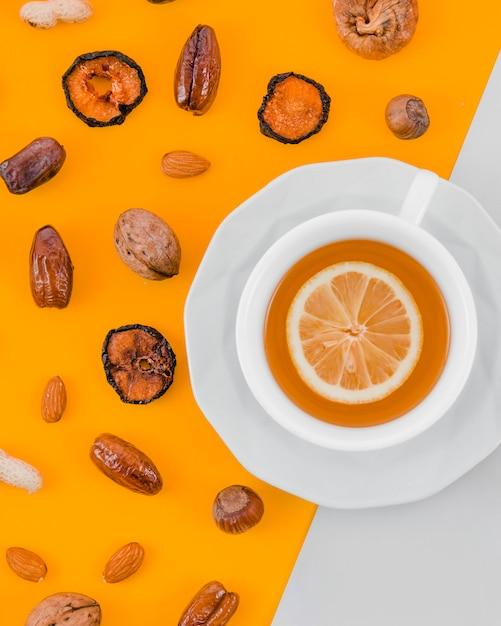 Getrocknete aprikose; termine; mandeln; nussbaum; erdnuss und haselnuss mit zitronenteetasse auf gelbem und weißem hintergrund Kostenlose Fotos