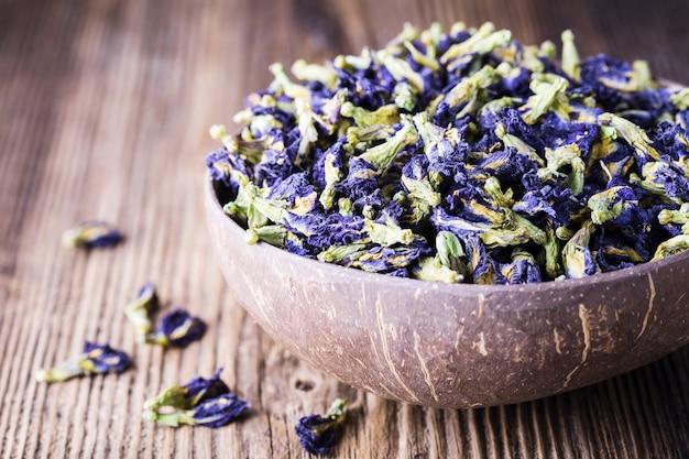 Getrocknete blaue schmetterlingserbsenblumen auf hölzernem hintergrund. Premium Fotos