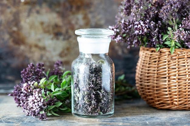 Getrocknete blumen von oregano in einer glasflasche auf einem holztisch. Kostenlose Fotos