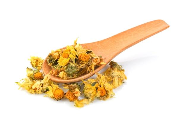 Getrocknete chrysanthemenblüten in holzlöffel Premium Fotos