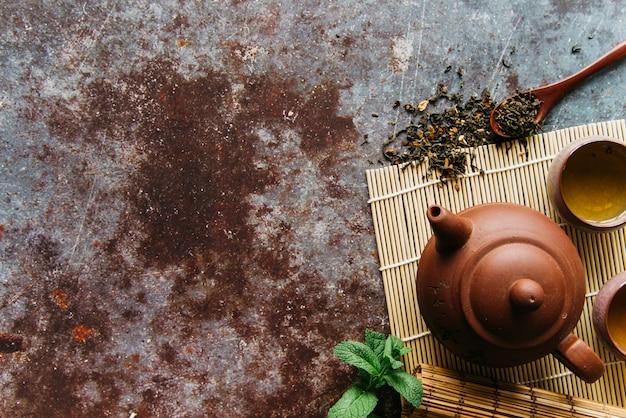 Getrocknete kräuter; minze; teekanne und kräutertee auf tischset über dem rustikalen hintergrund Kostenlose Fotos