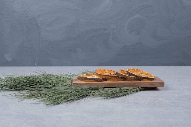 Getrocknete orange auf holzbrett mit zweig des grünen baumes. hochwertiges foto Kostenlose Fotos