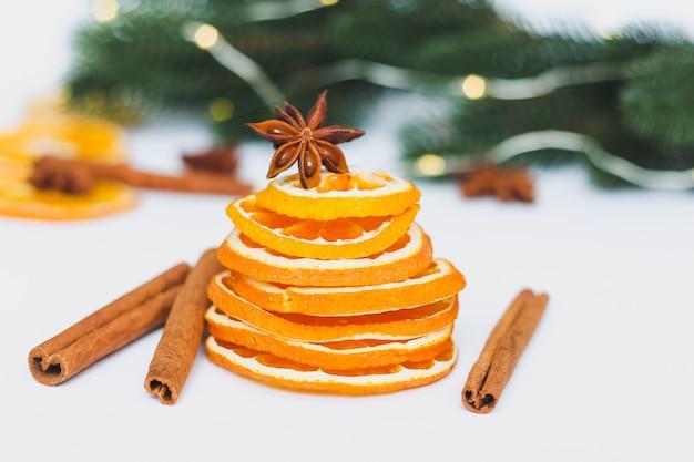 Getrocknete orangenscheiben mit weihnachtlichen tannenzweigen und gewürzen Premium Fotos