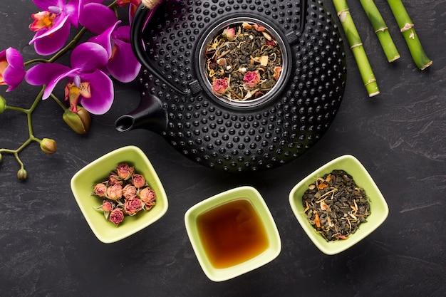 Getrocknete rosen und kräuterteebestandteil mit orchideenblume auf schwarzem hintergrund Kostenlose Fotos
