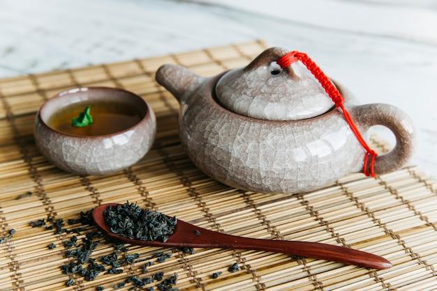 Getrocknete teeblätter mit keramischer teekanne und teetassen auf tischset Kostenlose Fotos