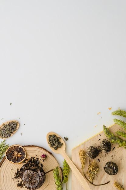 Getrocknete zitronenscheibe und verschiedene art von kräutern lokalisiert auf weißem hintergrund Kostenlose Fotos