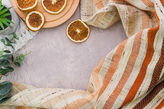Getrocknete zitronenscheiben mit streifengewebe auf konkretem hintergrund Kostenlose Fotos