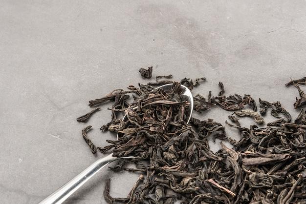 Getrockneter tee und ein löffel auf einem grauen strukturierten hintergrund. Premium Fotos