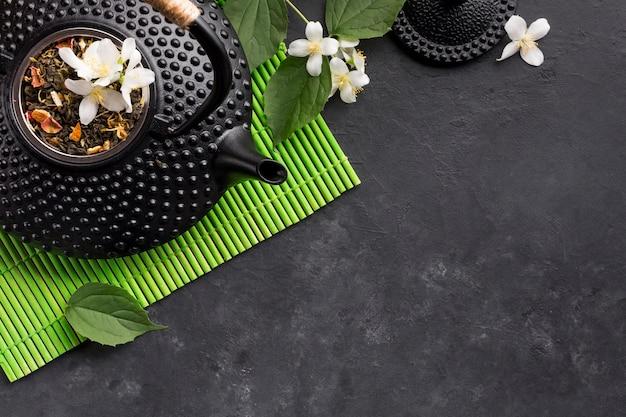 Getrocknetes teekraut und weiße jasminblume auf schwarzem hintergrund Kostenlose Fotos