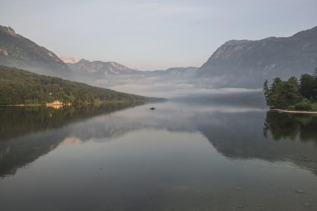 Gewässer nahe gebirgszügen mit der grünen vegetation bedeckt mit nebel während der tageszeit Kostenlose Fotos