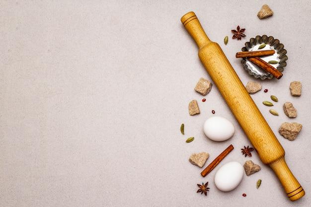 Gewürze, eier, brauner würfelzucker, cupcake-auflaufform und ein nudelholz. licht Premium Fotos