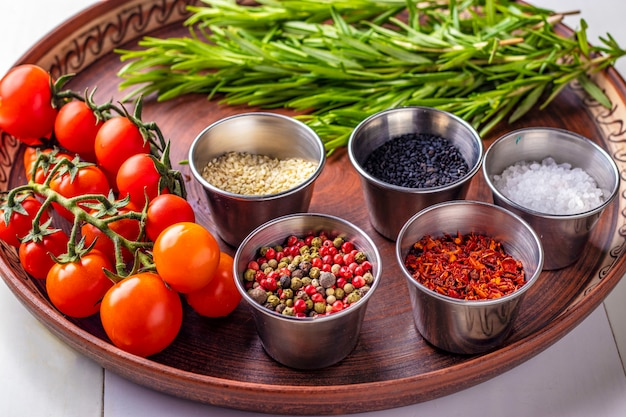 Gewürze: eine mischung aus paprika, paprikaflocken, meersalz, schwarzem und weißem sesam, rosmarin und kirschtomaten auf einer tellernahaufnahme Premium Fotos