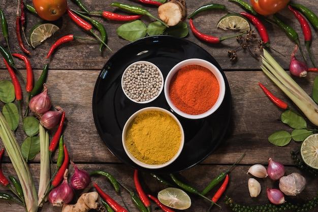 Gewürze mit bestandteilen auf hölzernem hintergrund. asiatisches essen, gesund oder kochkonzept. Premium Fotos