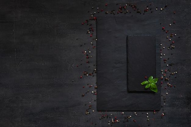 Gewürze und gewürze auf quadratischem steinbrett Premium Fotos