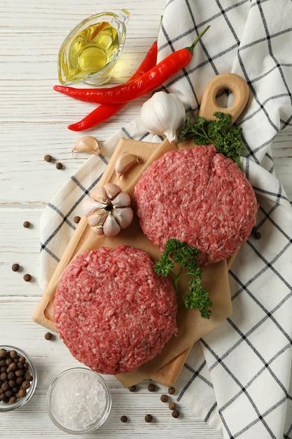 Gewürze und schneidebrett mit hackfleisch auf holz, draufsicht Premium Fotos
