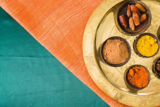 Gewürze und trockenfrüchte auf tablett auf textil Kostenlose Fotos
