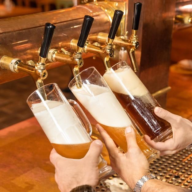 Gießen, füllen von biergläsern, becher aus dem fass Premium Fotos