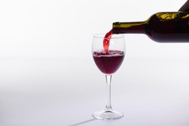 Gießen rotwein in das glas auf weißem hintergrund mit kopienraum Premium Fotos