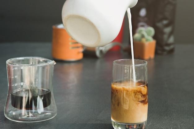 Gießen sie frische milch in eine schwarze kaffeetasse. Premium Fotos