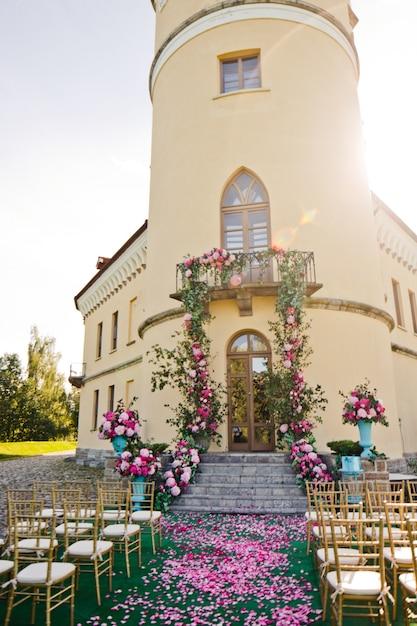 Girlanden von Grün und rosa Blüten hängen vom Balkon über die Treppe ...