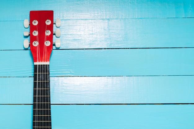 Gitarre auf einem hölzernen hintergrund Premium Fotos