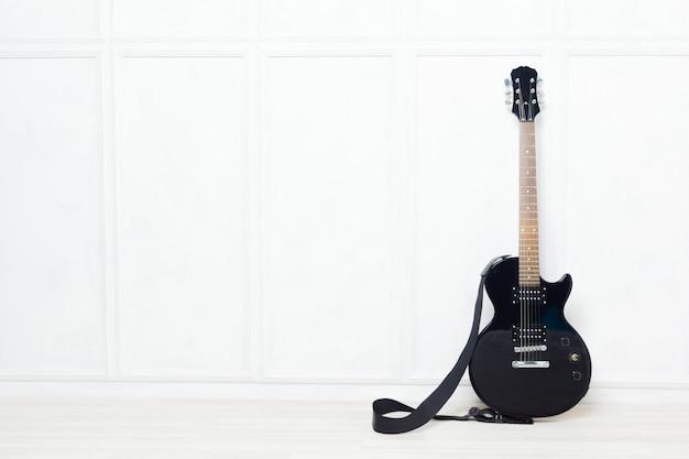 Gitarre vor einer weißen wand gestützt Premium Fotos