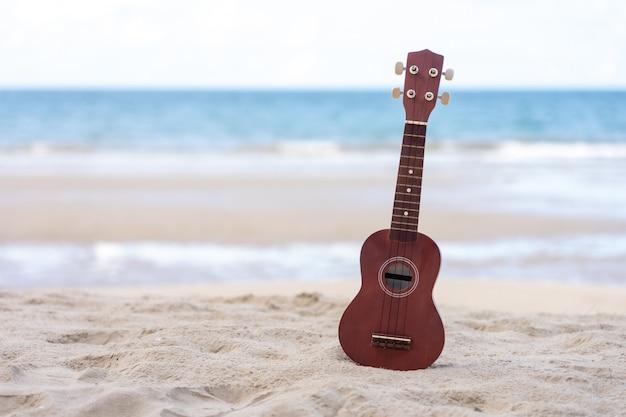 Gitarrenukulele setzte an den sandstrand. seeansicht während der tageszeit mit blauem himmel Premium Fotos
