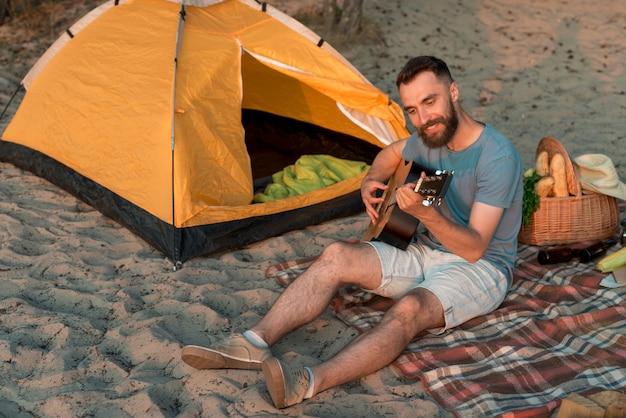 Gitarrist sitzt neben dem zelt Kostenlose Fotos
