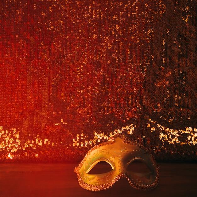 Glänzende karnevalsmaske gegen rot glitzerndes textilgewebe Kostenlose Fotos