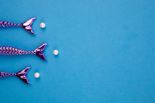 Glänzende schwänze von meerjungfrauen auf einem blauen hintergrund Premium Fotos