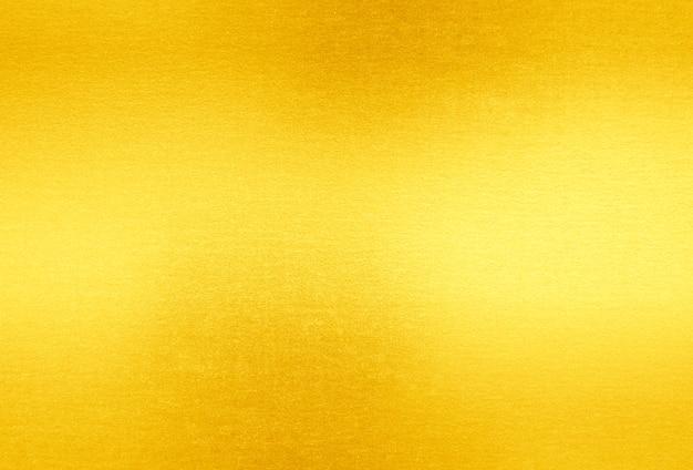 Glänzender gelber blattgoldfolien-beschaffenheitshintergrund Premium Fotos