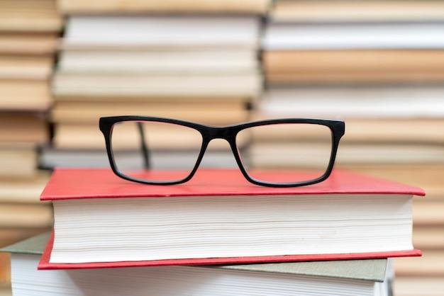 Gläser auf dem hintergrund der bücher. symbol für wissen, wissenschaft, studium, weisheit. Premium Fotos