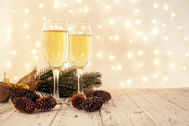 Gläser champagner auf einem holztisch mit einer verschwommenen goldenen girlande, silvester-konzept Premium Fotos
