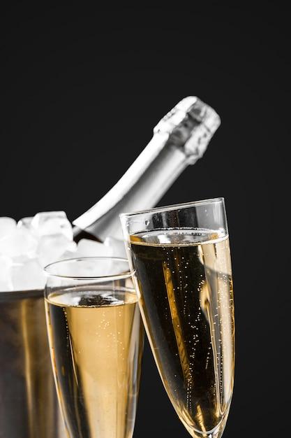 Gläser champagner mit einer champagnerflasche in einem eimer Premium Fotos