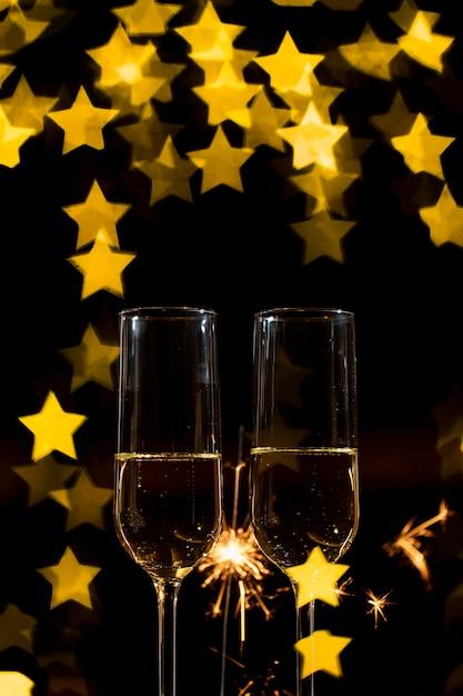 Gläser champagner mit feuerwerk und herzförmigem bokeh-effekt Kostenlose Fotos