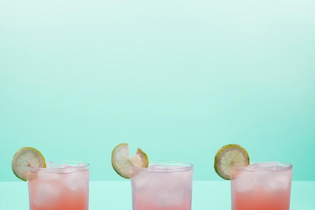 Gläser cocktail mit zitronenscheiben und eiswürfeln gegen tadellosen hintergrund Kostenlose Fotos