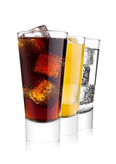 Gläser cola und orangensoda trinken und limonade mineralwasser auf weißem hintergrund mit eiswürfeln Premium Fotos