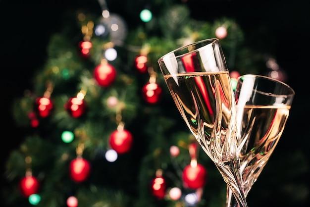Gläser des funkelnden champagners auf dem hintergrund eines geschmückten weihnachtsbaumes. Premium Fotos