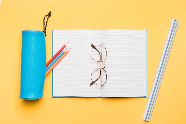 Gläser, die auf geöffnetem notizbuch mit leerseiten liegen Kostenlose Fotos