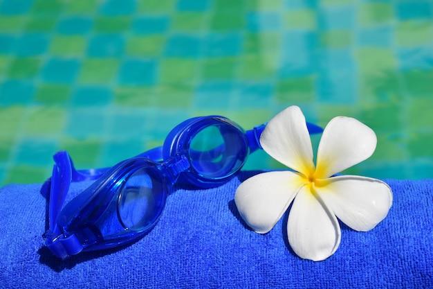 Gläser, handtücher und blumen auf dem wasser. sommerzeit und entspannung. Premium Fotos