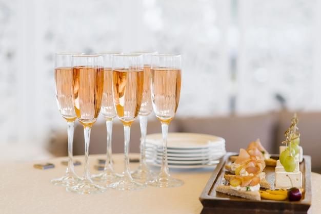 Gläser rosa champagner auf dem buffettisch mit imbissen Premium Fotos