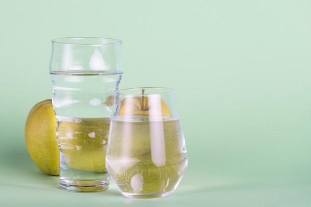 Gläser und apfel auf grünem hintergrund Kostenlose Fotos