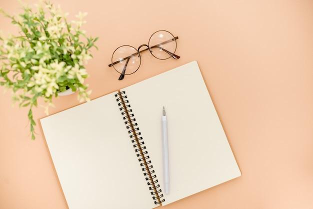 Gläser und notizblock auf einem beige abstrakten hintergrund Premium Fotos