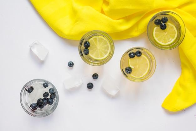 Gläser zitronensaft und eiswürfel mit gelbem gewebe auf weißem hintergrund Kostenlose Fotos