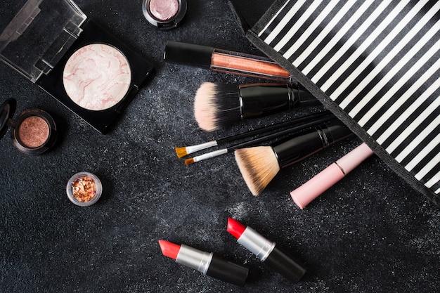 Glamour-kosmetik fiel aus dem gestreiften beutel Kostenlose Fotos