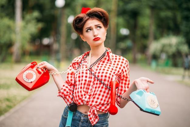 Glamour pin up girl mit retro-drehtelefonen, vintage amerikanische mode. attraktive frau im pinup-stil Premium Fotos